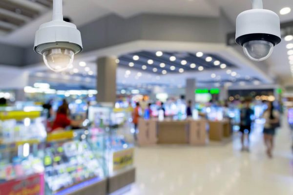 closeup-cctv-security-camera-on-blurred-inside-shopping-mall-background